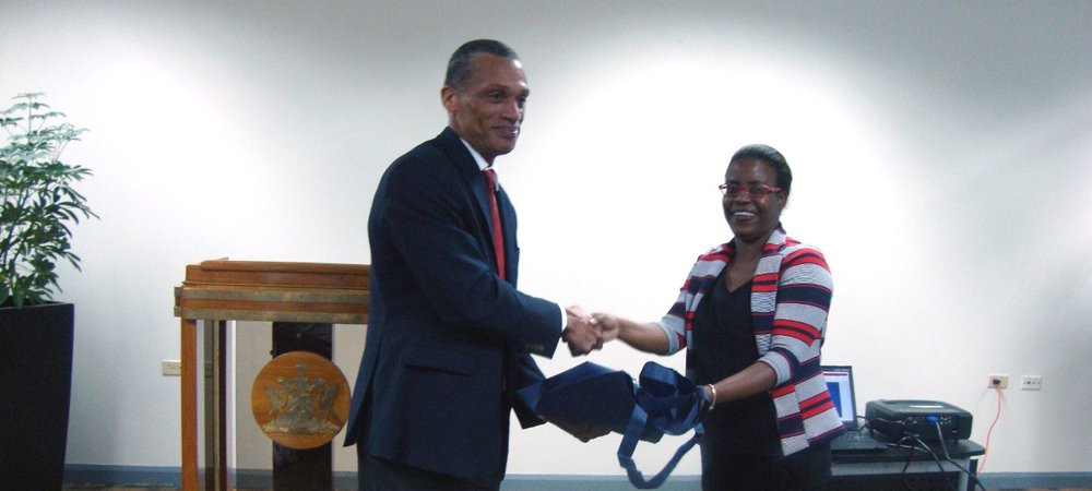Honourable Dennis Moses presents Ms. Natasha Second, Vice Principal of Bishops High School, Tobago with a token